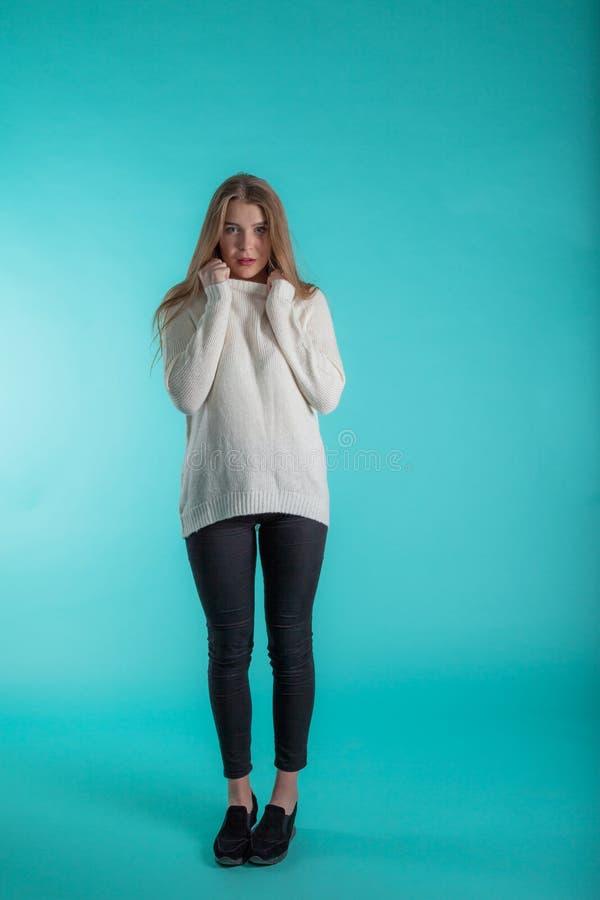 Consideravelmente fêmea com o cabelo longo, vestido ocasionalmente na camiseta do marfim, olhando com satisfação na câmera, no fu foto de stock