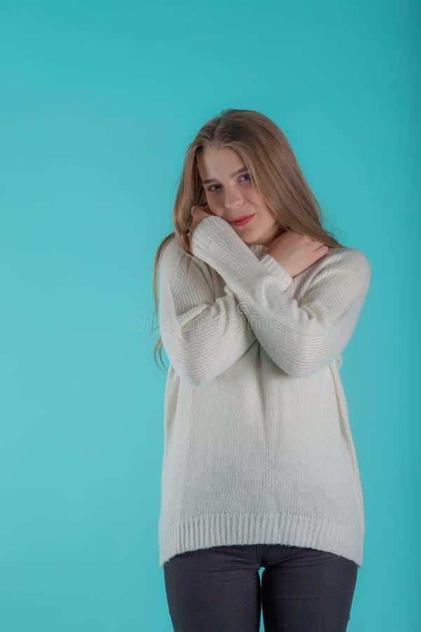 Consideravelmente fêmea com o cabelo longo, vestido ocasionalmente na camiseta do marfim, olhando com satisfação na câmera, no fu imagem de stock