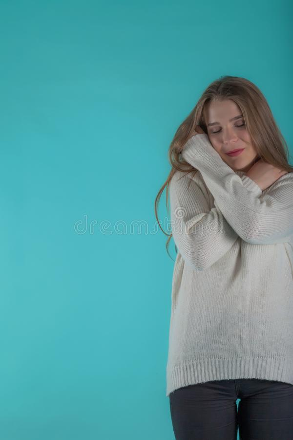 Consideravelmente fêmea com o cabelo longo, vestido ocasionalmente na camiseta do marfim, olhando com satisfação na câmera, no fu fotos de stock