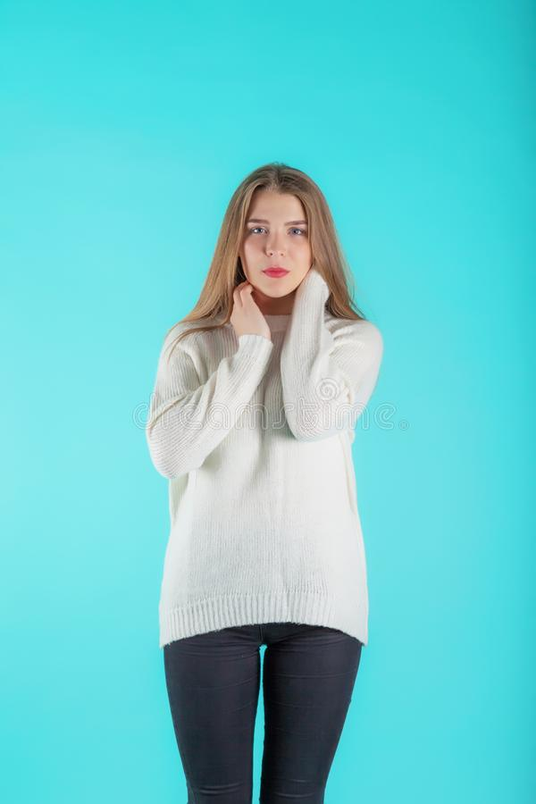 Consideravelmente fêmea com o cabelo longo, vestido ocasionalmente na camiseta do marfim, olhando com satisfação na câmera, no fu fotografia de stock