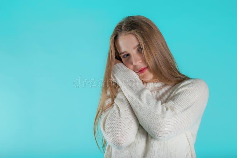 Consideravelmente fêmea com o cabelo longo, vestido ocasionalmente na camiseta do marfim, olhando com satisfação na câmera, no fu foto de stock royalty free