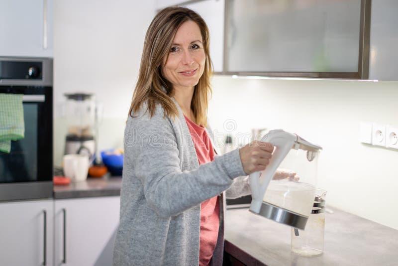 Consideravelmente, jovem mulher em sua cozinha brilhante moderna fotografia de stock