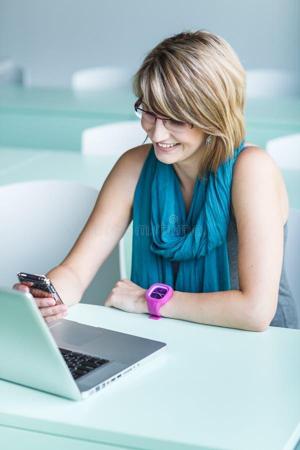 Consideravelmente, jovem mulher em um escritório, usando um portátil imagens de stock