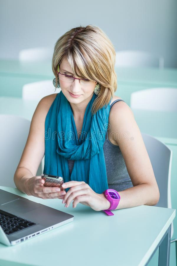 Consideravelmente, jovem mulher em um escritório, usando um portátil imagem de stock royalty free