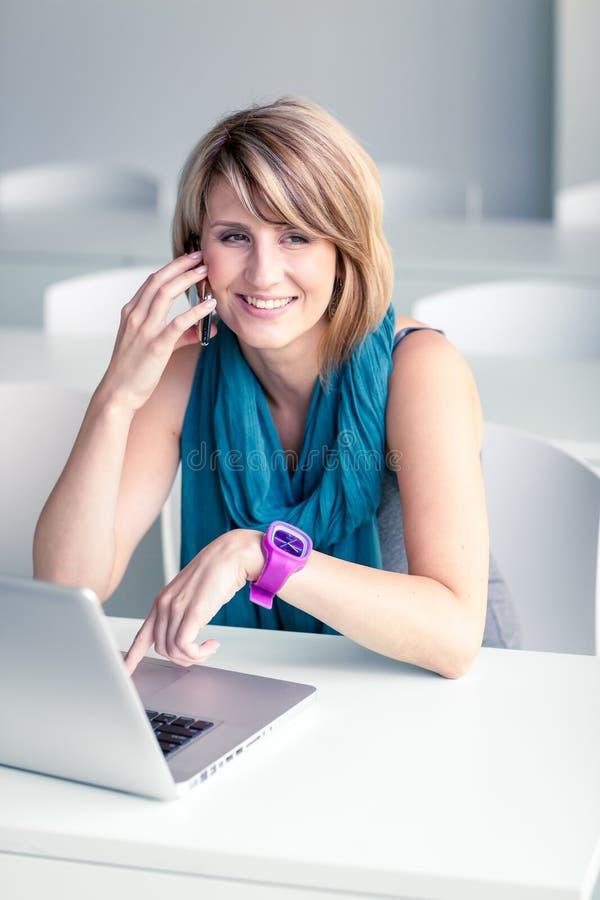 Consideravelmente, jovem mulher em um escritório, usando um portátil fotos de stock