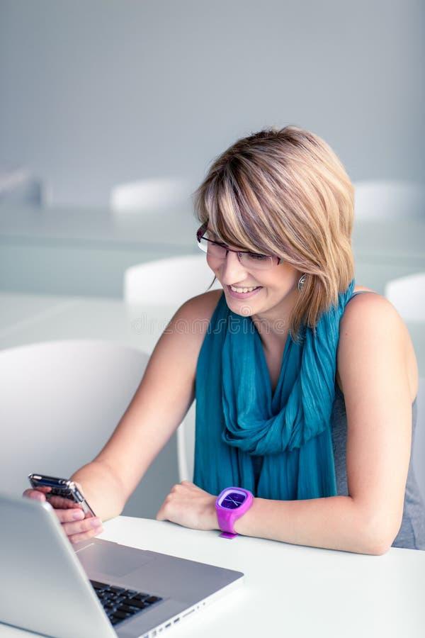 Consideravelmente, jovem mulher em um escritório, usando um portátil fotos de stock royalty free