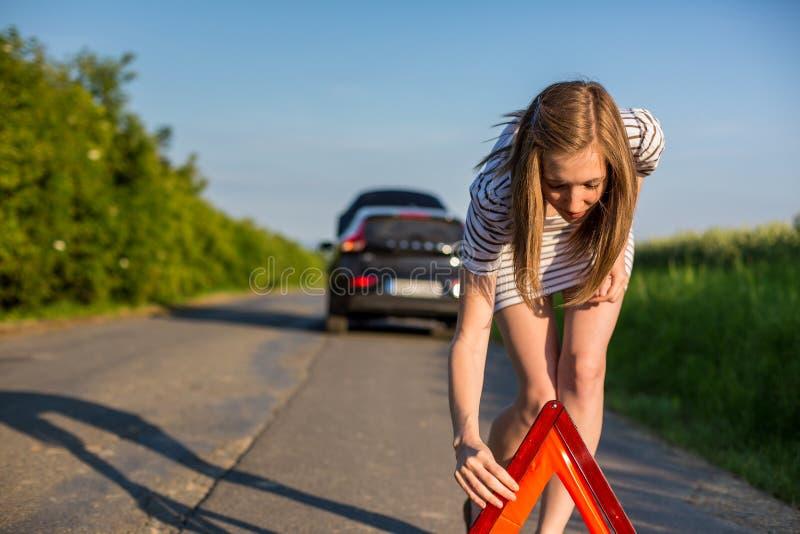 Consideravelmente, jovem mulher que ajusta o triângulo da segurança na borda da estrada imagem de stock royalty free