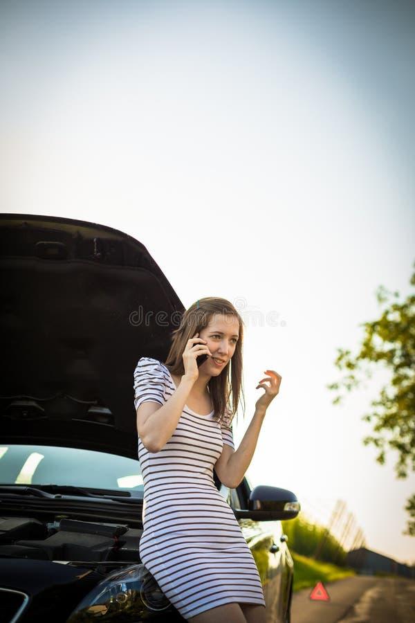 Consideravelmente, jovem mulher que chama o serviço da borda da estrada fotografia de stock royalty free