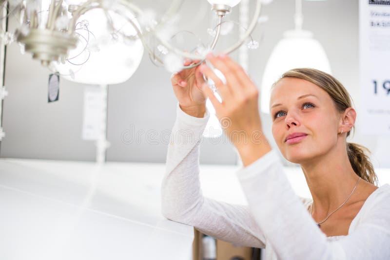 Consideravelmente, jovem mulher que escolhe a luz direita para seu apartamento imagem de stock
