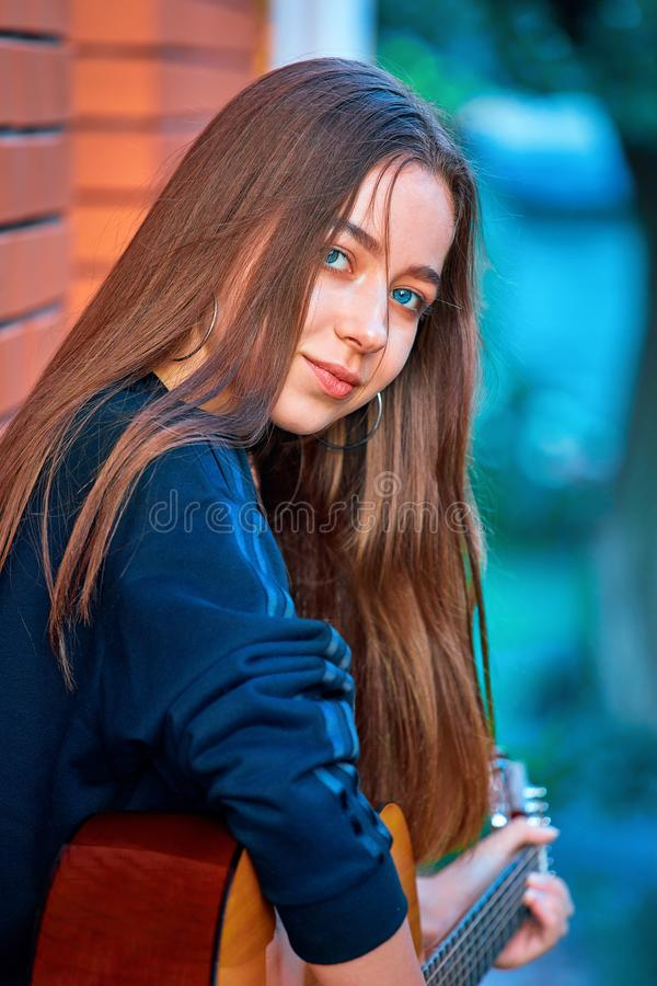 Consideravelmente, menina nova do adolescente que joga a guitarra Close-up fotografia de stock