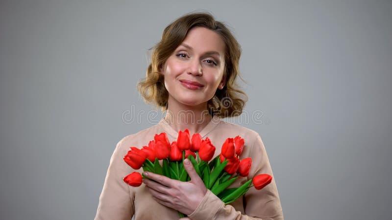 Consideravelmente senhora que guarda as flores que sorriem no fundo cinzento, presente de ?poca natal?cia, feminilidade fotografia de stock royalty free