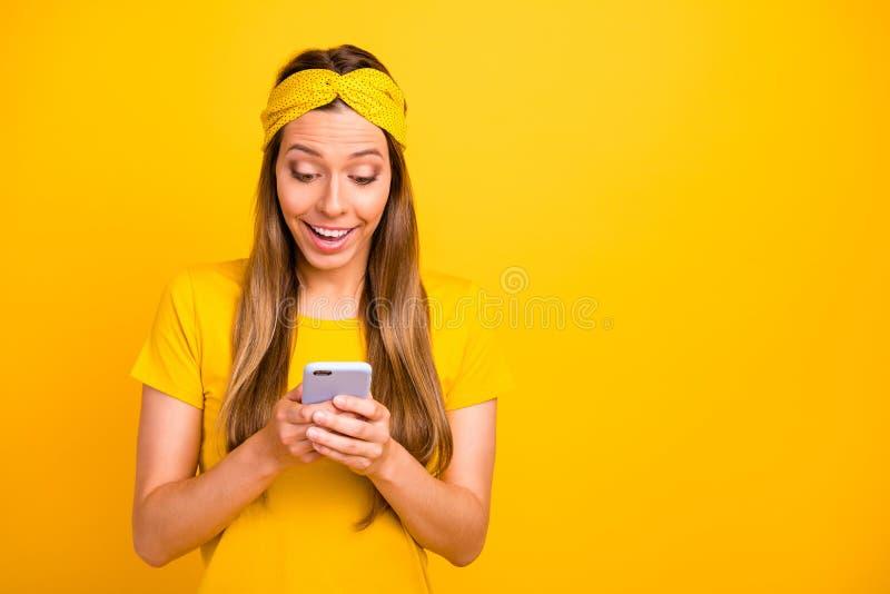 Consideravelmente senhora que guarda as mãos do telefone que olham o instagram afixar para vestir t-shirt ocasional o fundo amare fotos de stock