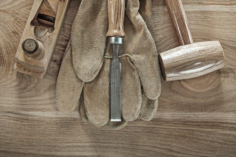 Considere luvas da segurança do formão da plaina do martelo na placa de madeira imagem de stock royalty free