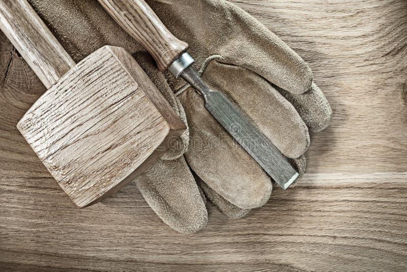 Considere luvas protetoras do couro do formão do martelo na placa de madeira fotografia de stock royalty free