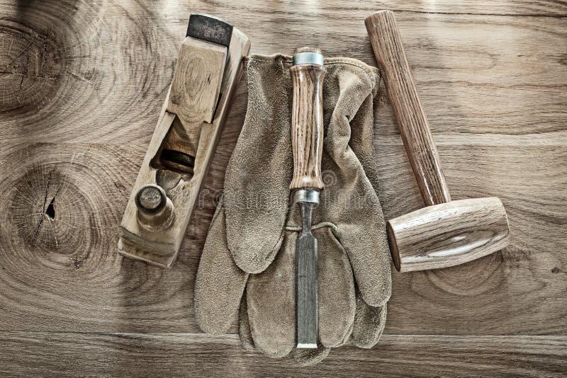 Considere o martelo que barbeia luvas planas da segurança do formão na placa de madeira imagem de stock