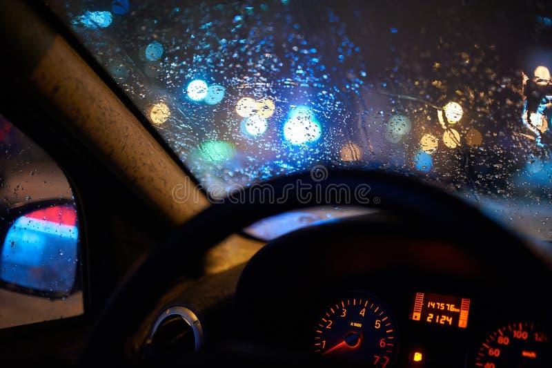Consideri la città bagnata tramite il parabrezza dall'interno dell'automobile al tempo della pioggia alla notte immagine stock