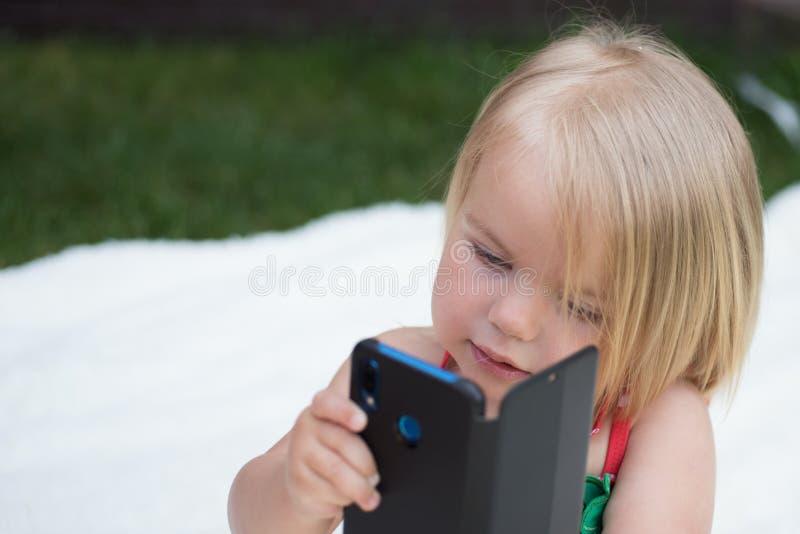 Consiga seu cabelo denominado durar o dia inteiro Criança da menina com conversa do cabelo louro no telefone celular Nova tecnolo imagem de stock