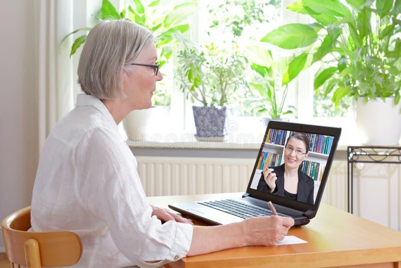 Consiglio online di imposta della donna senior fotografie stock