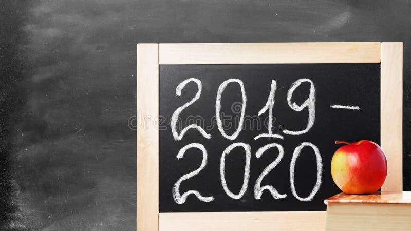 Consiglio scolastico con testo 2019 2020 Lavagna, mela e libro della scuola del fondo immagini stock libere da diritti