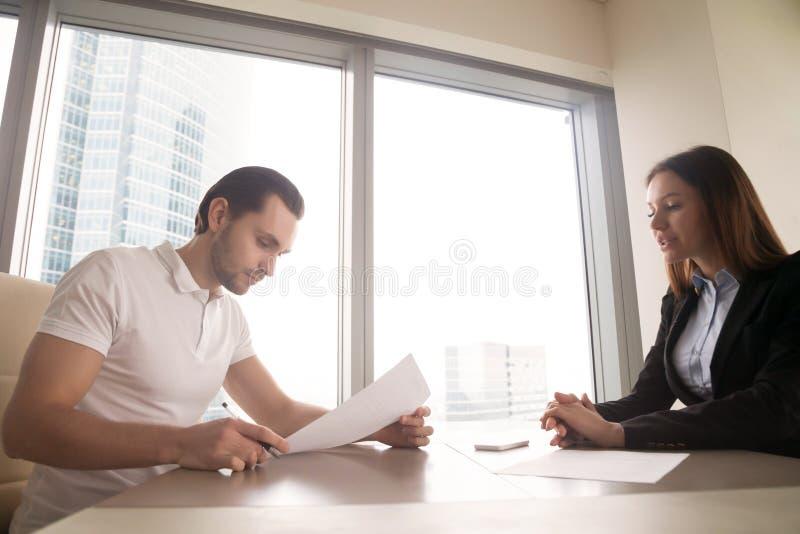 Consiguió un trabajo Hombre joven listo para firmar el contrato de funcionamiento imagen de archivo