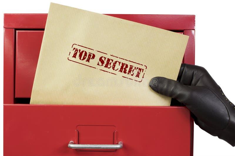 Consiguiendo documentos de alto secreto de un gabinete de fichero rojo, sobre un fondo blanco fotografía de archivo libre de regalías