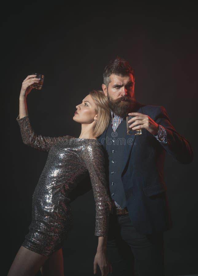 Consiguieron bebido en la celebración de días festivos de la oficina Hombre en traje y señora de lujo en la consumición corporati fotos de archivo libres de regalías