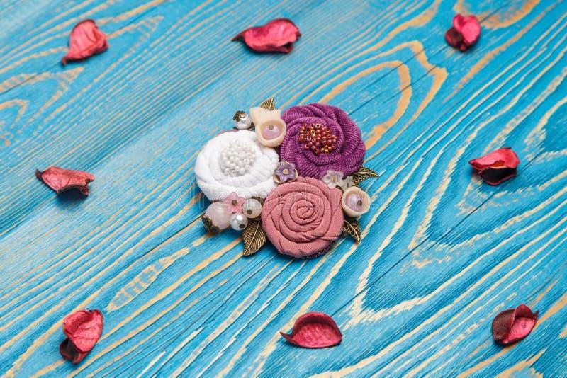 Consistir feito a mão do broche nas flores brancas, cor-de-rosa e lilás que fazem do pano no fundo azul fotos de stock royalty free