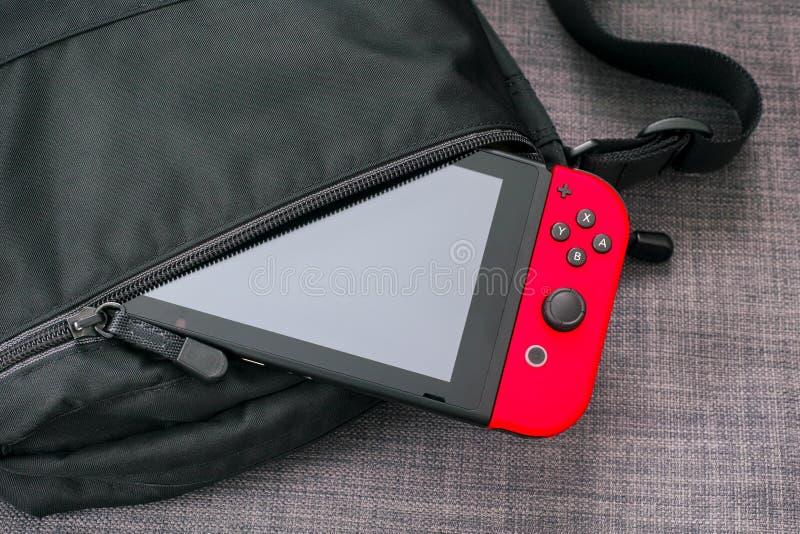 Consola del videojuego del interruptor de Nintendo en bolso negro imagenes de archivo