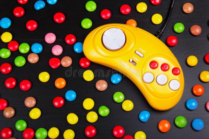 Consola GamePad del videojuego en una tabla de madera blanca Gamepad retro amarillo en un fondo de las grageas coloreadas del cho imágenes de archivo libres de regalías
