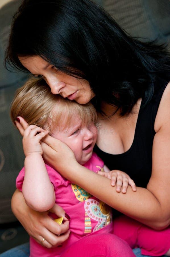Consolando um infante de grito foto de stock