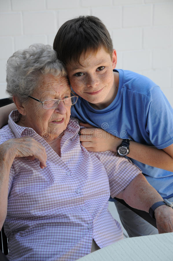 Consolation for grandma. Boy embraces and soothes his ninety years old grandma royalty free stock photos