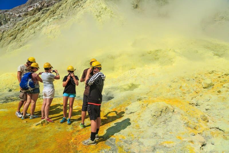 Console branco, Nova Zelândia Os turistas nos capacetes de segurança e nas máscaras de gás examinam poços derretidos do enxofre fotografia de stock