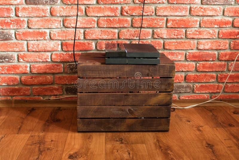 Console del gioco su una scatola di verdure contro la parete con fotografia stock