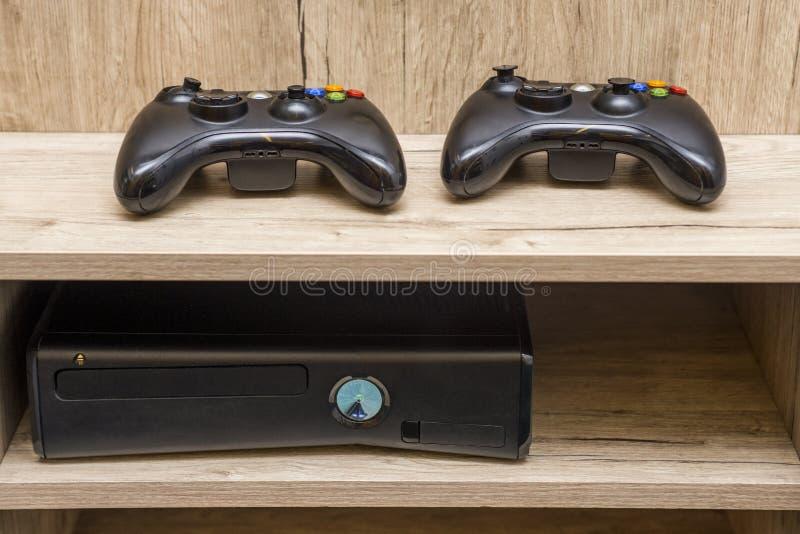 Console e controlador pretos do jogo a tabela Console e gamepad do jogo que encontram-se na tabela imagem de stock