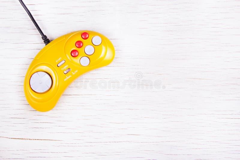 Console GamePad do jogo de vídeo em uma tabela de madeira branca GamePad retro amarelo imagens de stock