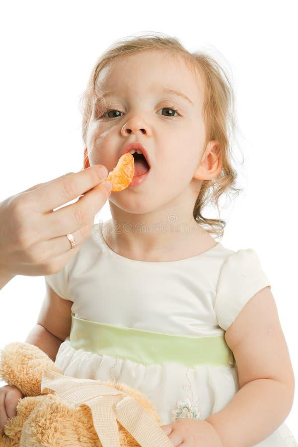 consommation de la mandarine de fille image stock
