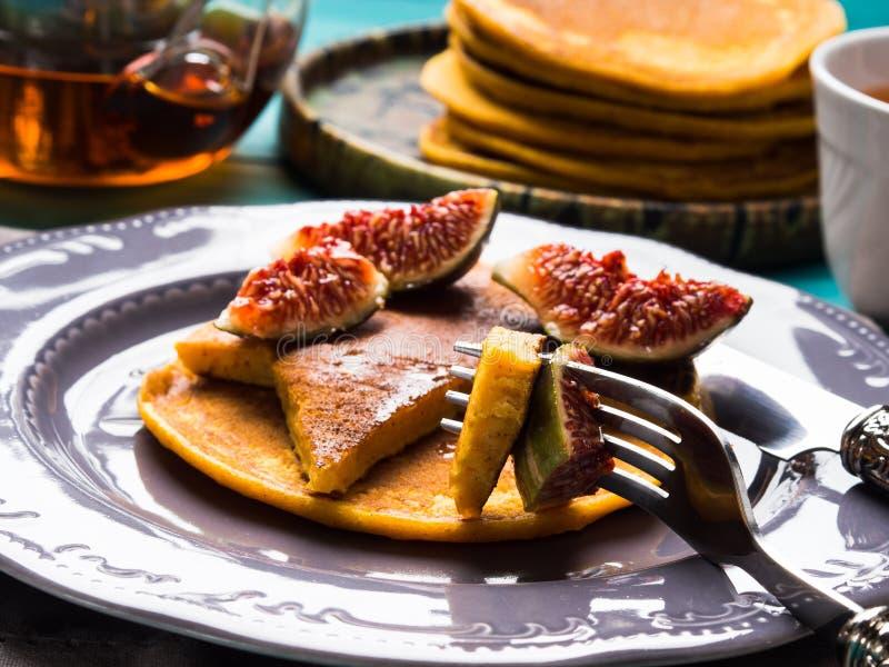 Consommation des crêpes de potiron avec les figues et le miel photo stock