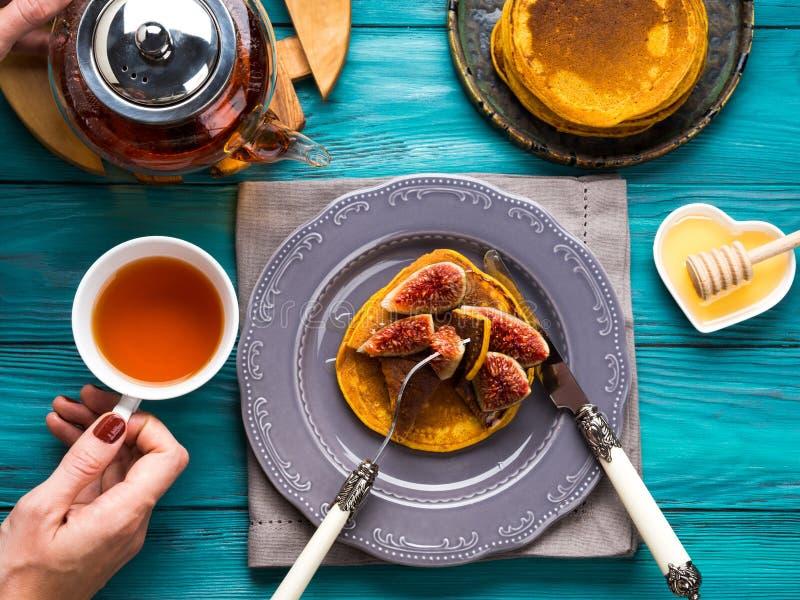 Consommation des crêpes de potiron avec les figues et le miel images libres de droits