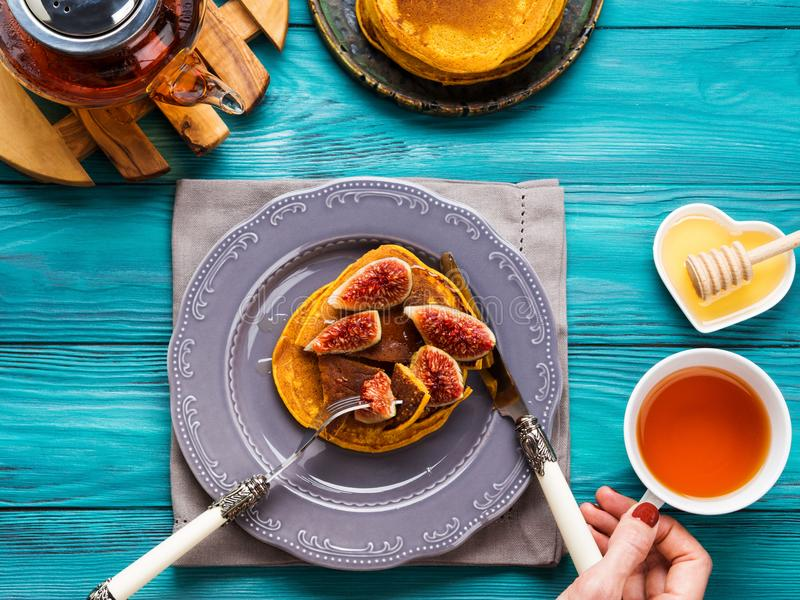 Consommation des crêpes de potiron avec les figues et le miel image stock