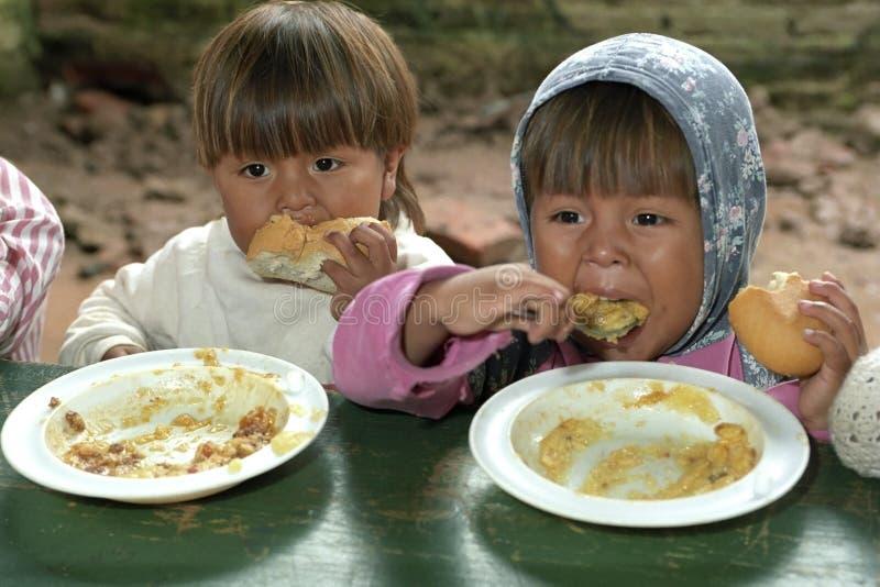 Consommation des enfants pendant la distribution de produits alimentaires photos libres de droits