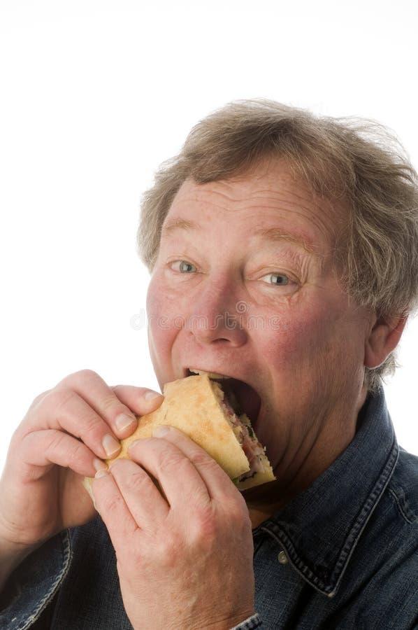 consommation du grand sandwich à homme images stock