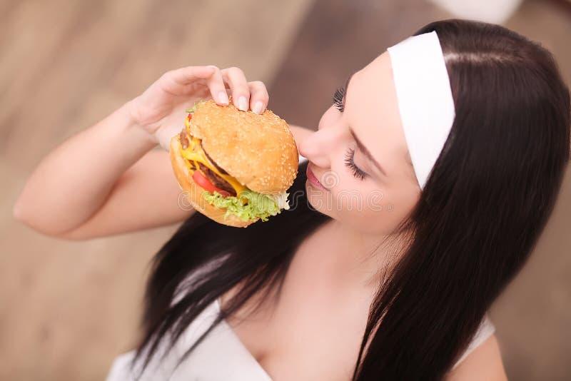Consommation malsaine Concept de nourriture industrielle Portrait de jeune femme à la mode tenant l'hamburger et posant au-dessus photographie stock