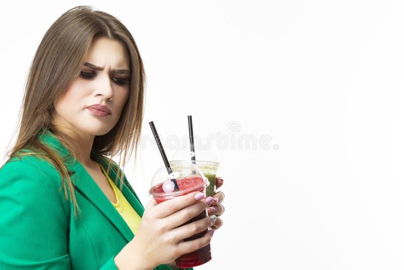 Consommation saine de nourriture Femme de pensée délicate avec le Smoothie végétal de Detox vert et rouge Pose dans la veste vert image libre de droits