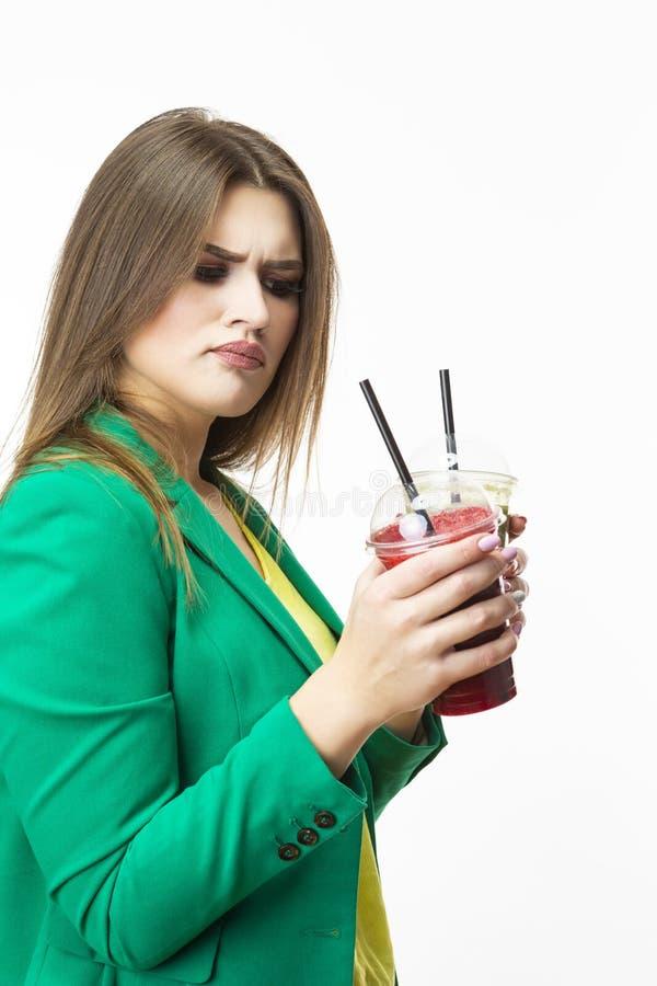 Consommation saine de nourriture Femme de pensée délicate avec le Smoothie végétal de Detox vert et rouge Pose dans la veste vert photos stock