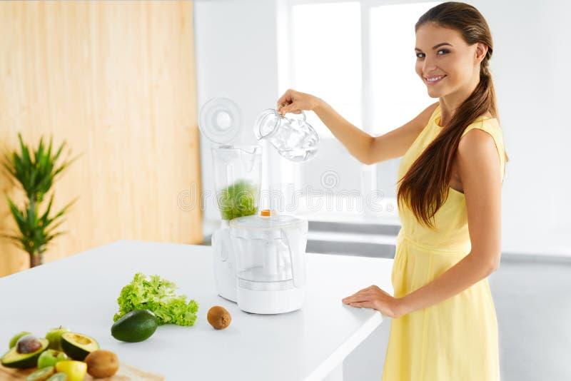 Consommation saine Femme végétarienne préparant le jus vert de Detox Régime, nourriture image stock