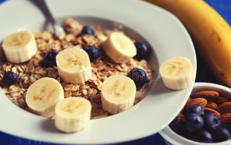 Consommation saine, nourriture et concept de régime - farine d'avoine avec des baies, des écrous et des bananes, plat blanc, fond images stock