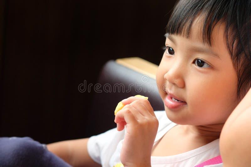 Consommation se reposante de fille asiatique mignonne heureusement image stock