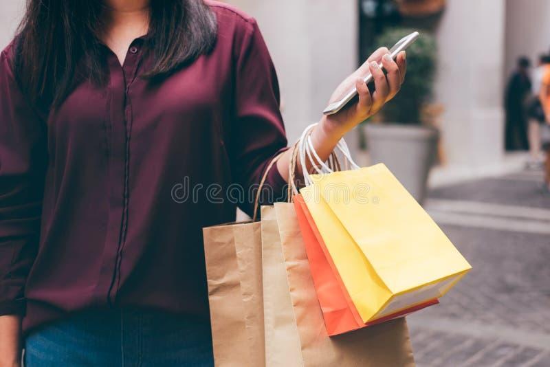 Consommationisme, achats, concept de mode de vie, jeune femme jugeant les paniers colorés et le smartphone appréciant dans les ac photo stock