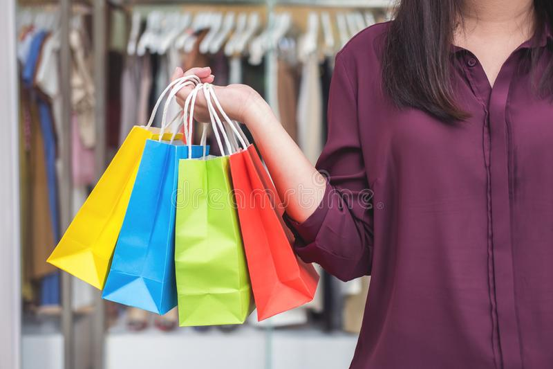 Consommationisme, concept de achat de mode de vie, jeune femme tenant et tenant les paniers colorés appréciant dans les achats photos libres de droits