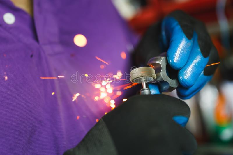 Constant-velocity CV joint gear with sparks, polishing with rotary tool. Close-up view royalty free stock images